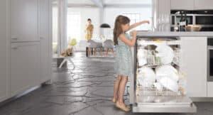 Mädchen räumt Geschirrspüler ein