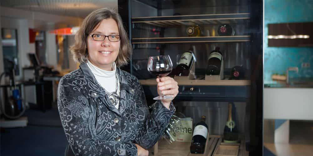 Christiane Richter mit Glas Rotwein vor Ausstellungsküche
